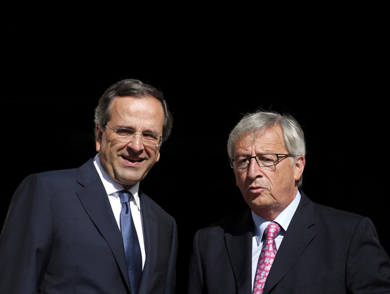 Greek Prime Minister, Antonis Samaras, left, welcomes Jean Claude Junker, Prime Minister of Luxembourg and President of Eurogroup prior to their meeting in Athens, Wednesday, Aug. 22, 2012. Juncke insisted Greece must remain within the euro. Its exit from the currency used by 17 European Union countries would hurt both the country and the wider continent. (AP Photo/Petros Giannakouris)