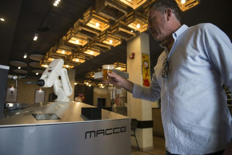 The robotic arm has been serving up small draft beers -- or canas -- for just over a week in the centre of Seville (AFP Photo/CRISTINA QUICLER)