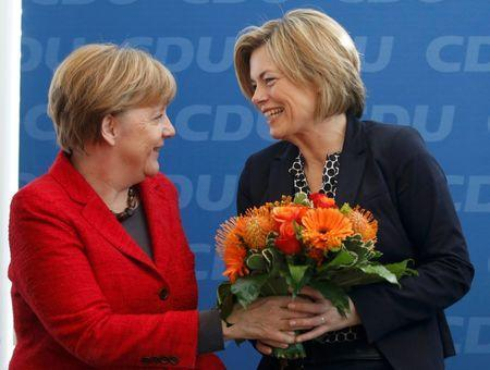 German Chancellor and leader of the Christian Democratic Union (CDU) Angela Merkel, presents flowers to Julia Kloeckner (R) top candidate in the Rheinland-Palatinate state election, at a party board meeting in Berlin, Germany March 14, 2016. REUTERS/Fabrizio Bensch