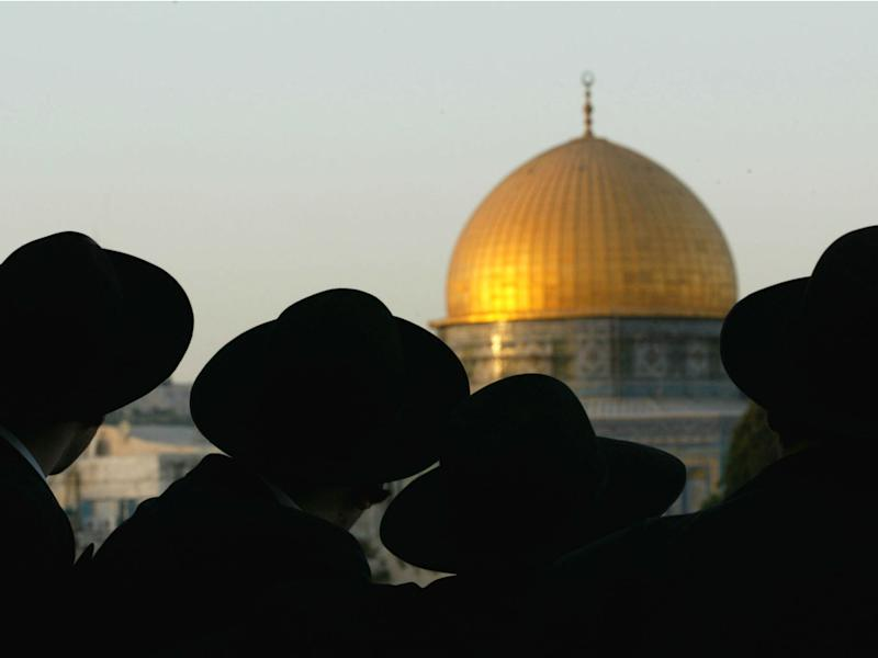 Ultra-Orthodox Jews look at the Dome of the Rock, one of the holiest sites for Muslims, in Jerusalem on August 8, 2002: Reuters