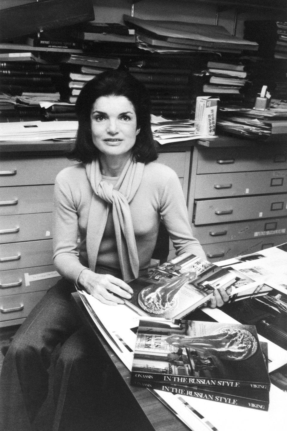 <p>That working-woman style was just as chic as you would imagine. Here is Jackie in her office at Viking Press wearing trousers and a sweater with neck wrap detail that someone needs to put back in production asap.</p>