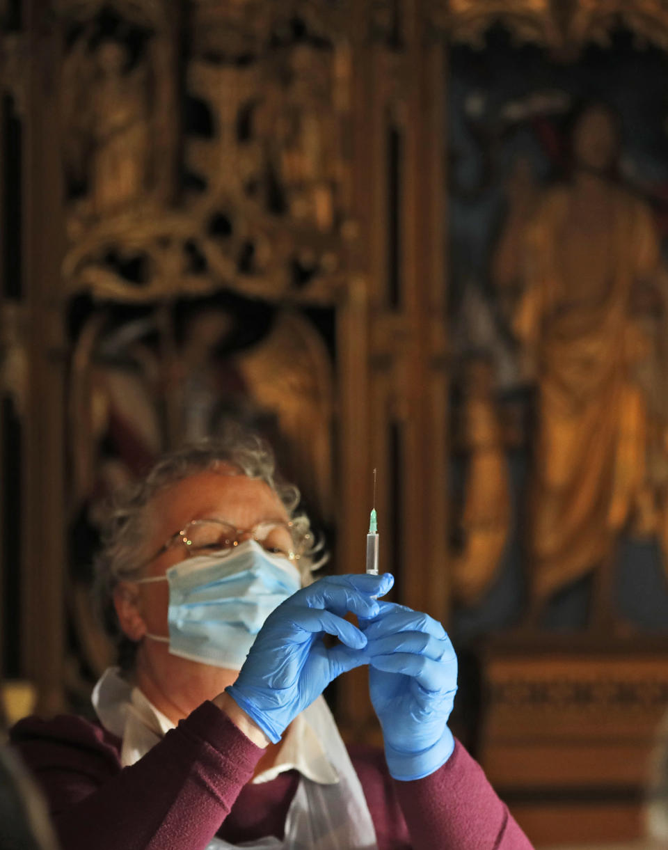A health worker prepares the Pfizer-BioNTech vaccine inside Salisbury Cathedral in Salisbury, England, Wednesday, Jan. 20, 2021. Salisbury Cathedral opened its doors for the second time as a venue for the Sarum South Primary Care Network COVID-19 Local Vaccination Service. (AP Photo/Frank Augstein)