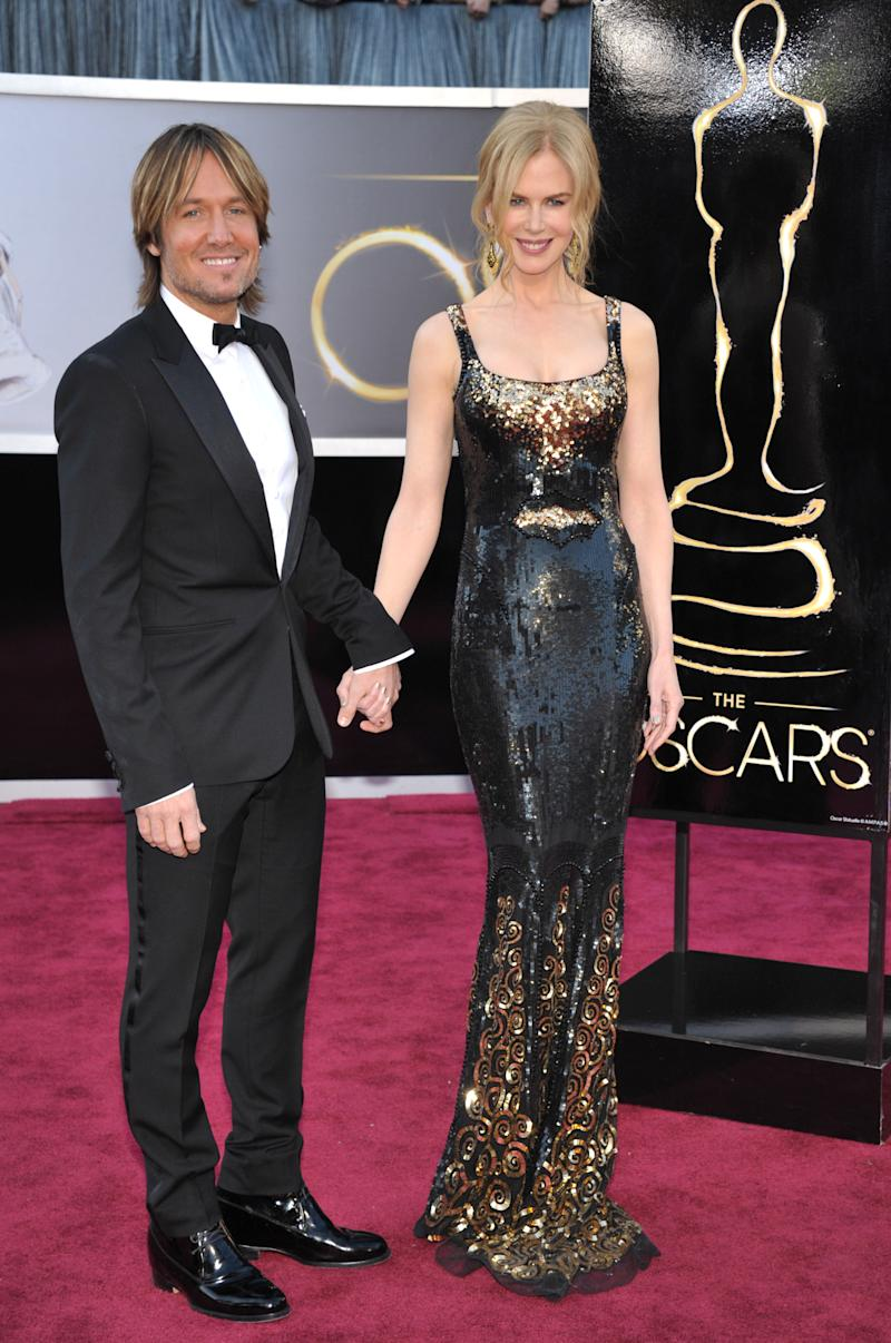 """FILE - This Feb. 24, 2013 file photo shows musician Keith Urban, left, and his wife actress Nicole Kidman at the Oscars at the Dolby Theatre in Los Angeles. urban is a judge on the singing competition series, """"American Idol,"""" airing Wednesdays and Thursdays on Fox. (Photo by John Shearer/Invision/AP, file)"""