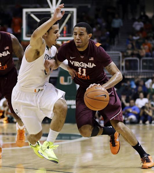 Miami's Shane Larkin (0) tries to steal the ball from Virginia Tech's Erick Green (11) during the first half of an NCAA college basketball game in Coral Gables, Fla., Wednesday, Feb. 27, 2013. (AP Photo/J Pat Carter)