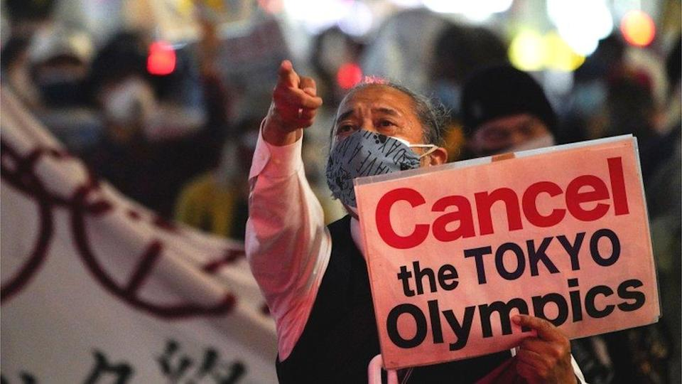 Man with banner calling for the Olympics to be cancelled