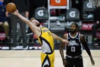 Indiana Pacers forward Domantas Sabonis (11) reaches for a rebound near Los Angeles Clippers guard Paul George (13) during the second quarter of an NBA basketball game, Sunday, Jan. 17, 2021, in Los Angeles. (AP Photo/Ashley Landis)