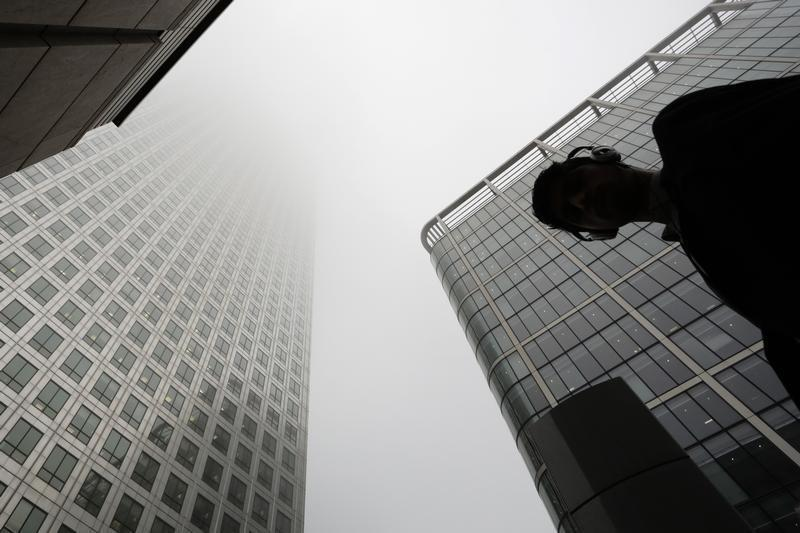 Man walks past a building in the morning mist at London's financial district of Canary Wharf