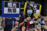 """Chow Hang Tung, Vice Chairperson of the Hong Kong Alliance in Support of the Democratic Patriotic Movements of China, speaks to media after being released on bail at a police station in Hong Kong, Saturday, June 5, 2021. Hong Kong police on Friday, June 4, arrested Chow for publicizing an unauthorized assembly via social media despite the police ban on the annual June 4 candlelight vigil. The placards read: """"Innocent of candlelight."""" (AP Photo/Kin Cheung)"""