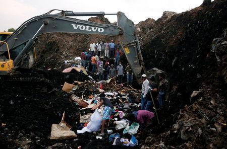 Rescue workers watch as excavators dig into a pile of garbage in search of missing people following a landslide when a mound of trash collapsed on an informal settlement at the Koshe garbage dump in Ethiopia's capital Addis Ababa, March 13, 2017. REUTERS/Tiksa Negeri