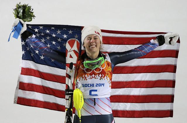 Women's slalom gold medal winner Mikaela Shiffrin of the United States poses for photographers with the American flag at the Sochi 2014 Winter Olympics, Friday, Feb. 21, 2014, in Krasnaya Polyana, Russia.(AP Photo/Christophe Ena)
