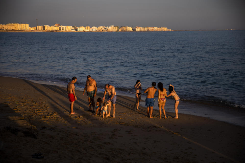 People enjoy the beach in Cadiz, south of Spain, on Friday, July 24, 2020. With the coronavirus rebounding in parts of Spain, it appears that several regions have not adequately prepared to trace new infections in what was supposed to be an early detection system to prevent a new cascade of cases. (AP Photo/Emilio Morenatti)