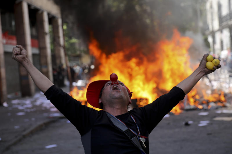 An anti-government demonstrator screams in font of a burning barricade in Santiago, Chile, Tuesday, Oct. 22, 2019. (Photo: Rodrigo Abd/AP)