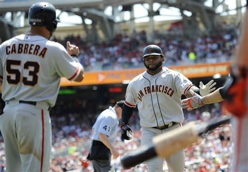 San Francisco Giants' Pablo Sandoval, right, is greeted by teammates including Melky Cabrera (53) after he hit a two-run home run during the first inning of a baseball game against the Washington Nationals, Wednesday, July 4, 2012, in Washington. (AP Photo/Nick Wass)