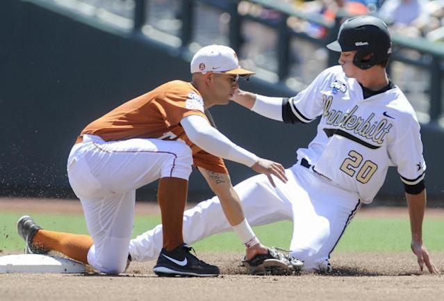 Vanderbilt left fielder Bryan Reynolds (20) reaches second base on a wild pitch against Texas shortstop C.J Hinojosa, left, in the first inning of an NCAA baseball College World Series game in Omaha, Neb., Friday, June 20, 2014. (AP Photo/Eric Francis)