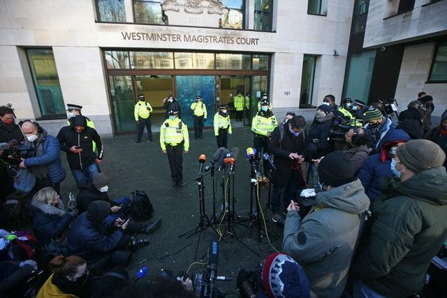Police officers and members of the media outside Westminster Magistrates' Court, London