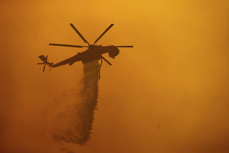 A helicopter drops water on the Fawn Fire burning north of Redding in Shasta County, Calif., on Thursday, Sept. 23, 2021. (AP Photo/Ethan Swope)