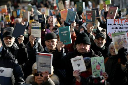 People raise science books outside the Hungarian Academy of Sciences to protest against government plans to weaken the institution in Budapest, Hungary, February 12, 2019. REUTERS/Tamas Kaszas