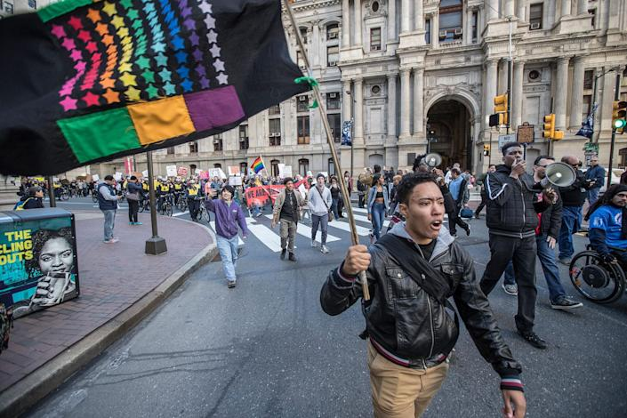 <p>Sam Marks waves a flag of diversity as he and the other protesters participate in march Monday, Feb. 20, 2017, in Philadelphia. Thousands of demonstrators turned out Monday across the U.S. to challenge Donald Trump in a Presidents Day protest dubbed Not My President's Day. (Michael Bryant/The Philadelphia Inquirer via AP) </p>