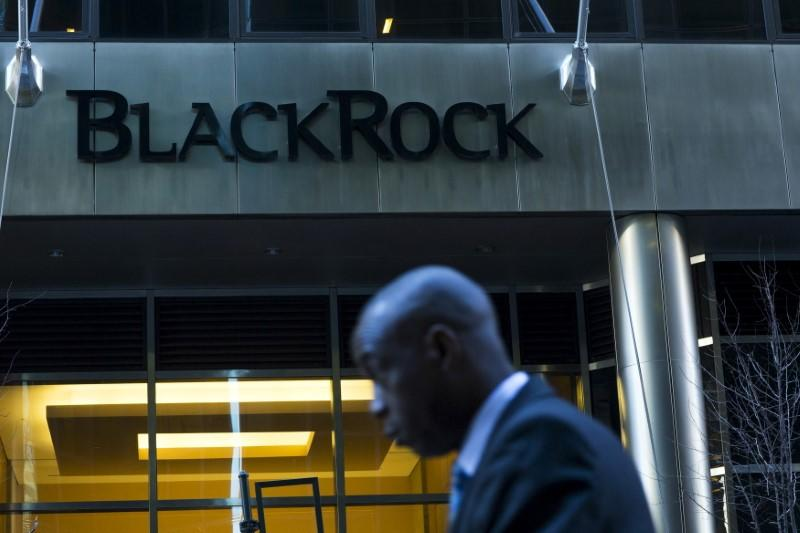 A man walks next to a BlackRock sign pictured in the Manhattan borough of New York