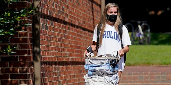 "Freshman Sarah Anne Cook carries her belongings as she packs to leave campus following a cluster of COVID-19 cases at the University of North Carolina in Chapel Hill, North Carolina. <p class=""copyright"">AP Photo/Gerry Broome</p>"
