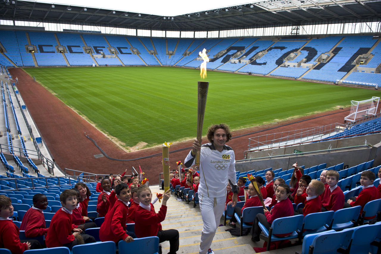 In this handout image provided by LOCOG, Torchbearer 005 and Trialthlete Tim Don carries the Olympic Flame in the stands of the City of Coventry Stadium during day 45 of the Olympic Flame Torch Relay on July 2, 2012 in Coventry, England. The Olympic Flame is now on day 45 of a 70-day relay involving 8,000 torchbearers covering 8,000 miles.  (Photo by LOCOG via Getty Images)