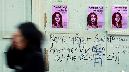 File photograph of a woman walking past posters advertising a candlelit vigil for a woman who was denied a termination and later died at the University Hospital Galway in Galway