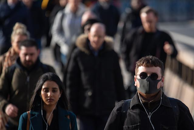 A man wearing a protective face mask as commuters cross London Bridge. (PA Images)