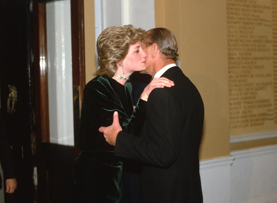 LONDON, ENGLAND - MARCH 19: Diana, Princess of Wales, wearing a green velvet dress designed by Victor Edelstein and an emerald choker necklace, kisses her father-in-law, Prince Philip, Duke of Edinburgh on the cheek as she arrives to attend a dinner at the Royal Society of Arts on March 19, 1986 in London, United Kingdom. (Photo by Anwar Hussein/Getty Images)