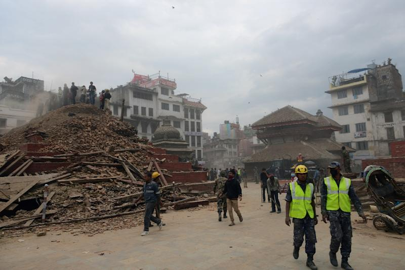 Nepalese rescue workers and onlookers gather at Kathmandu's Durbar Square, which was severely damaged by a 7.8 magnitude earthquake on April 25, 2015