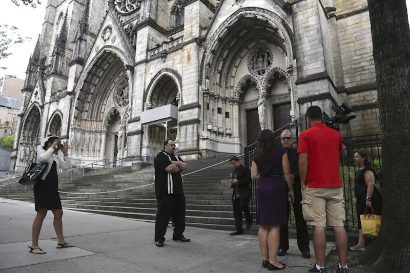 """Reporters interview members of the public outside the Cathedral Church of Saint John the Divine for the funeral service for James Gandolfini, Thursday, June 27, 2013 in New York. Gandolfini, who played Tony Soprano in the HBO show """"The Sopranos"""", died while vacationing in Italy last week. (AP Photo/Mary Altaffer)"""