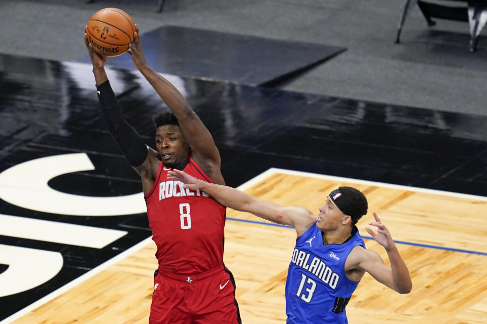 Houston Rockets forward Jae'Sean Tate (8) grabs a rebound over Orlando Magic guard R.J. Hampton (13)during the second half of an NBA basketball game, Sunday, April 18, 2021, in Orlando, Fla. (AP Photo/John Raoux)
