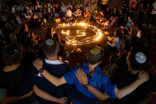 People gather around candles during a vigil in Tel Aviv in memory of the 45 ultra-Orthodox Jews killed in the stampede