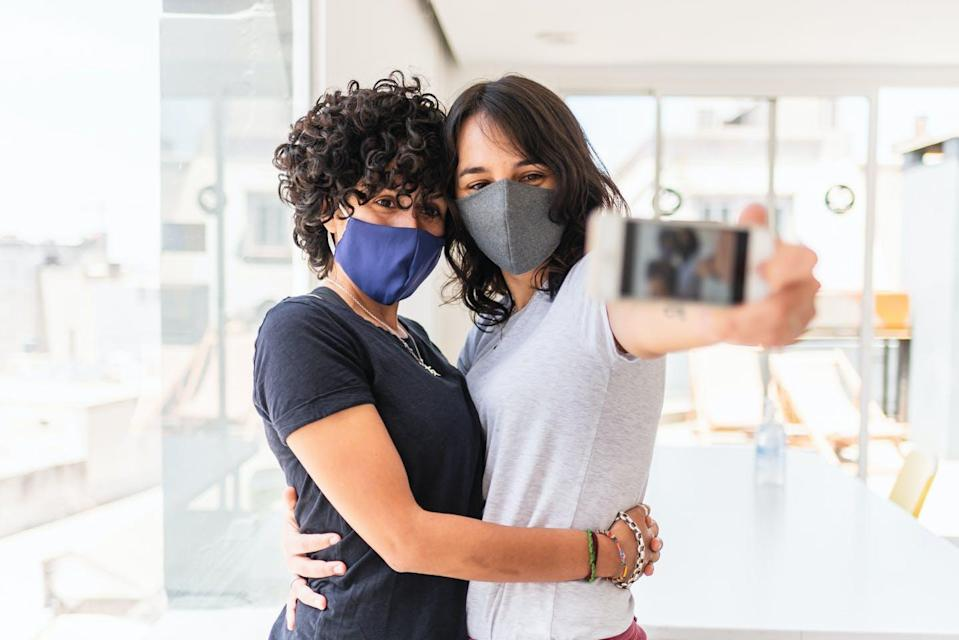 Two women wearing face masks pose for a selfie