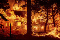 Flames from the Dixie Fire consume a home in the Indian Falls community of Plumas County, Calif., Saturday, July 24, 2021. The fire destroyed multiple residences as it tore through the area. (AP Photo/Noah Berger)