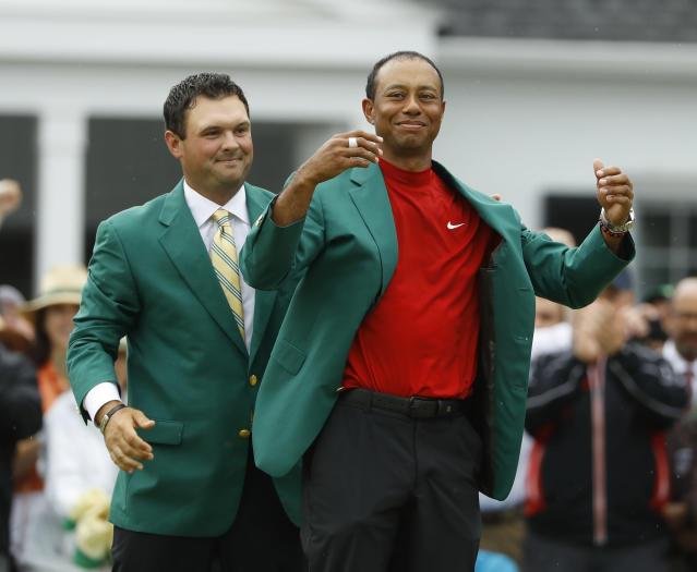 FILE - In this April 14, 2019, file photo, Patrick Reed, left, helps Tiger Woods with his green jacket after Woods won the Masters golf tournament, in Augusta, Ga. The annual rite of spring for golf won't happen this year. The Masters has been postponed until a later date. Augusta National did not indicate when the Masters would be played. That means there will be no golf at least for the next month. The Masters began in 1934 and only World War II has kept it from being played. This was the biggest shoe to drop for golf. The PGA Tour already canceled the next three events leading up to the Masters. Tiger Woods was to be going after his sixth green jacket. (AP Photo/Matt Slocum, File)