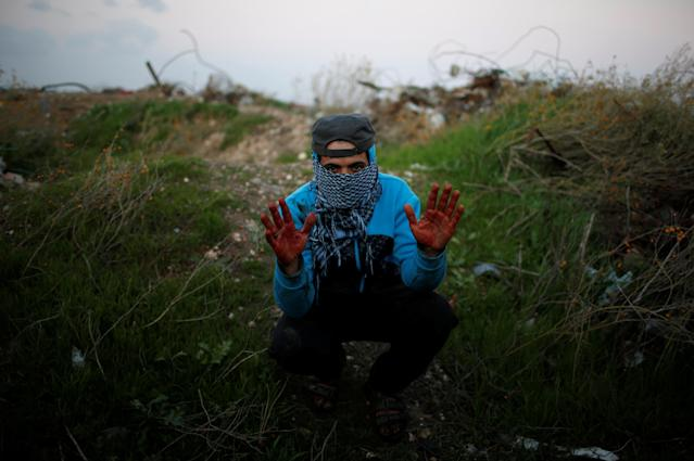 """<p>A Palestinian protester, nicknamed Abu Jaber, gestures with his hands stained with the blood of a wounded friend as he poses for a photograph at the scene of clashes with Israeli troops near the border with Israel, east of Gaza City, Jan. 19, 2018. """"We protest against the crazy decision made by Trump on Jerusalem and against the hardship we have experienced for more than 10 years due to the Israeli blockade. I hope the blood which you can see on my hands will move the Arab and Muslim world to revolt against Israel and America,"""" said Abu Jaber. (Photo: Mohammed Salem/Reuters) </p>"""