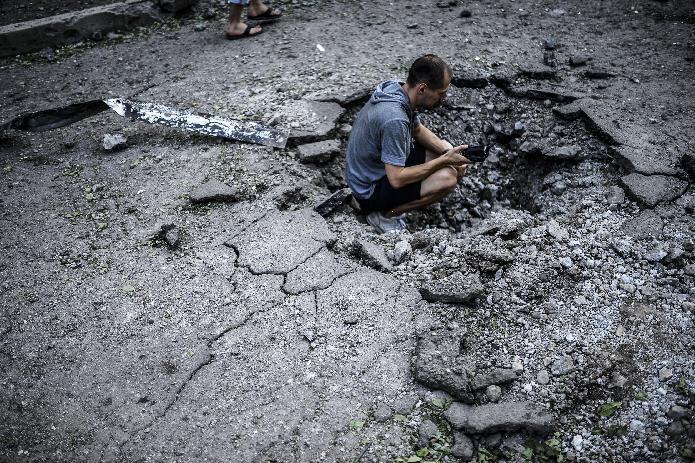A Ukrainian man videos a shell crater in Donetsk, on July 29, 2014 (AFP Photo/Bulent Kilic)