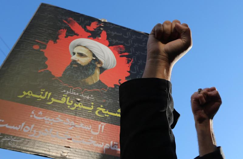 Protesters raise their fists in front of a portrait of prominent Shiite Muslim cleric Nimr al-Nimr during a demonstration against his execution by Saudi authorities, on January 3, 2016: Getty
