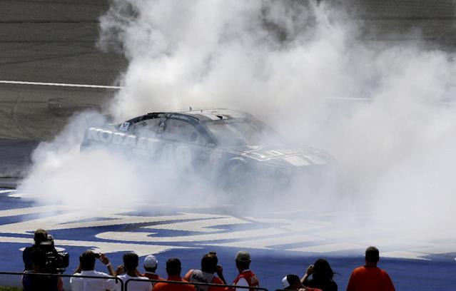 Driver Jimmie Johnson burns rubber after winning the NASCAR Quicken Loans 400 series auto race at Michigan International Speedway in Brooklyn, Mich., Sunday, June 15, 2014. (AP Photo/Carlos Osorio)