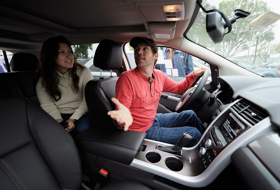 Allen Zimney and his girlfriend Leila Alvarez with the help of Star Ford salesman Greg Bowles shop for a Ford Edge at the Star Ford dealership, (Photo by Kevork Djansezian/Getty Images)
