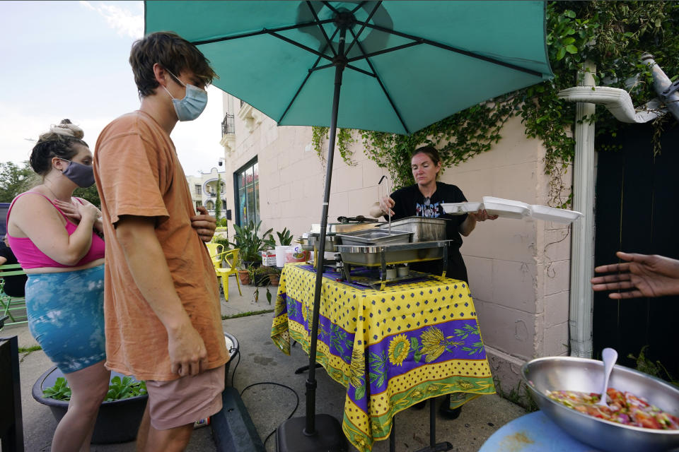 """In this Wednesday, Sept. 1, 2021, photo, El Pavo Real restaurant owner Lindsey McLellan, right, used food preserved """"with ice and prayer"""" to serve up a free steak taco meal, in New Orleans, La. In New Orleans, food is just one of the many ways that residents help each other during hard times. And it's been no different in the days after Hurricane Ida, which flooded or destroyed homes, tore up trees and knocked out the entire city's power grid. (AP Photo/Eric Gay)"""