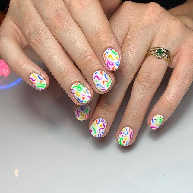 """<p>Scribble some neon designs on a white base for nails straight out of the early '90s. </p><p><a href=""""https://www.instagram.com/p/CDzPNmWjuu3/"""" rel=""""nofollow noopener"""" target=""""_blank"""" data-ylk=""""slk:See the original post on Instagram"""" class=""""link rapid-noclick-resp"""">See the original post on Instagram</a></p>"""