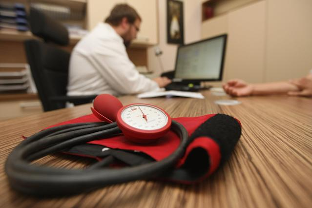 A doctor speaks to a patient as a sphygmomanometer, or blood pressure meter, lies on his desk. (Photo: Adam Berry/Getty Images)