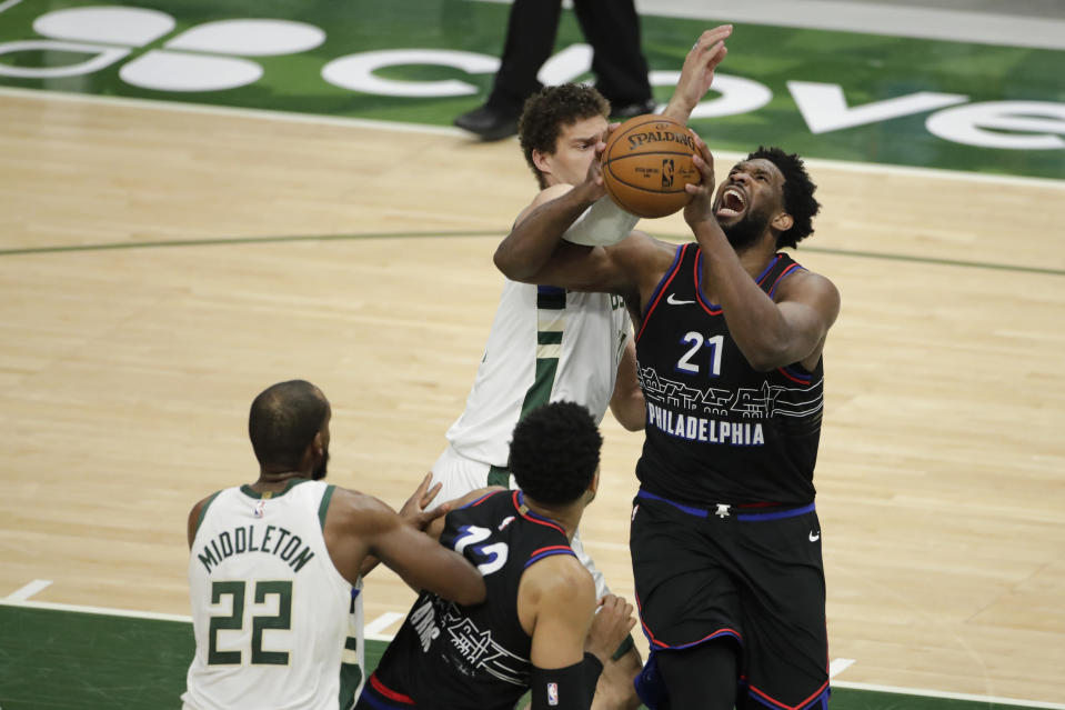 Philadelphia 76ers' Joel Embiid (21) drives to the basket next to Milwaukee Bucks' Brook Lopez during the second half of an NBA basketball game Thursday, April 22, 2021, in Milwaukee. (AP Photo/Aaron Gash)