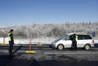 Policemen check documents of a driver near the city of Sokolov, Czech Republic, Friday, Feb. 12, 2021. Almost 600 police officers were deployed to enforce a complete lockdown of the three hardest-hit counties on the border with Germany and Poland to help contain a fast-spreading variant of the coronavirus found in Britain. (AP Photo/Petr David Josek)