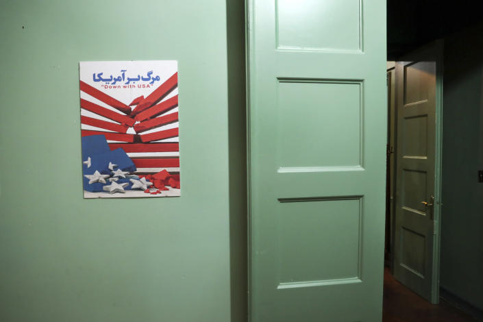 In this Sept. 26, 2019 photo, an anti-U.S. placard adorns a corridor of the former U.S. Embassy in Tehran, now partly a museum, in Tehran, Iran. The diplomatic compound was overrun by students angered when Washington allowed ousted Shah Mohammad Reza Pahlavi into the U.S. for medical treatment. What initially began as a sit-in devolved into 444 days of captivity for 52 Americans seized in the embassy. (AP Photo/Vahid Salemi)