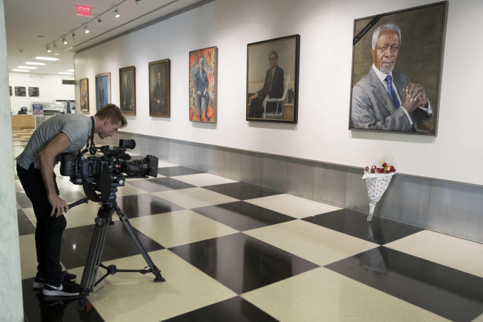 A journalist films the black ribbon and a bouquet of flowers adorning the portrait of former United Nations Secretary-General Kofi Annan at U.N. headquarters, Saturday, Aug. 18, 2018. Annan, one of the world's most celebrated diplomats and a charismatic symbol of the United Nations who rose through its ranks to become the first black African secretary-general, has died. He was 80. (AP Photo/Mary Altaffer)
