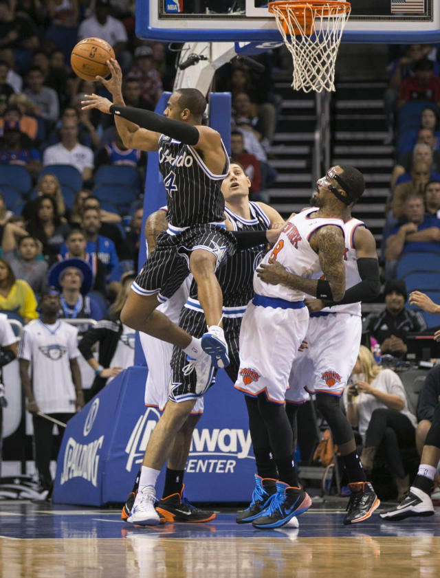 Orlando Magic's Arron Afflalo (4) passes the ball while guarded by New York Knicks' J.R. Smith (8) during overtime of an NBA basketball game in Orlando, Fla., Friday, Feb. 21, 2014. The Magic won 129-121 in two overtimes. (AP Photo/Willie J. Allen Jr.)