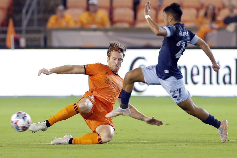 Houston Dynamo defender Tim Parker, left, attempts to kick away the ball as Vancouver Whitecaps midfielder Ryan Raposo (27) moves to the goal during the second half of an MLS soccer match Saturday, May 22, 2021, in Houston. (AP Photo/Michael Wyke)