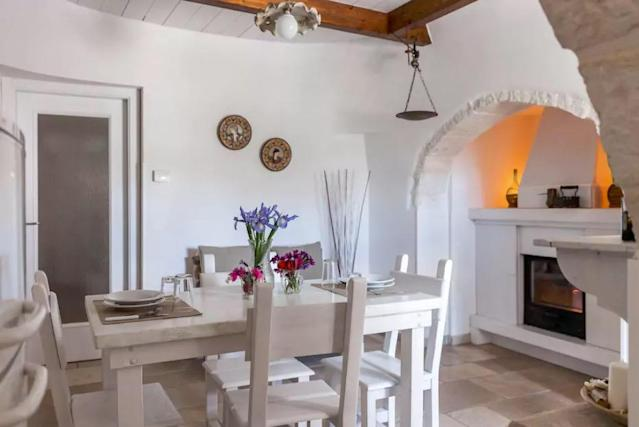 <p>The home's eating area is picturesque, with the table in front of a modernized fireplace.<br>(Airbnb) </p>